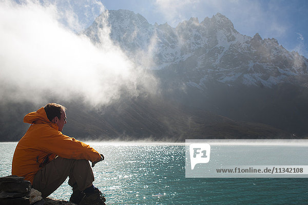 A trekker in the Everest region looks out over Gokyo Lake  Khumbu Region  Nepal  Asia