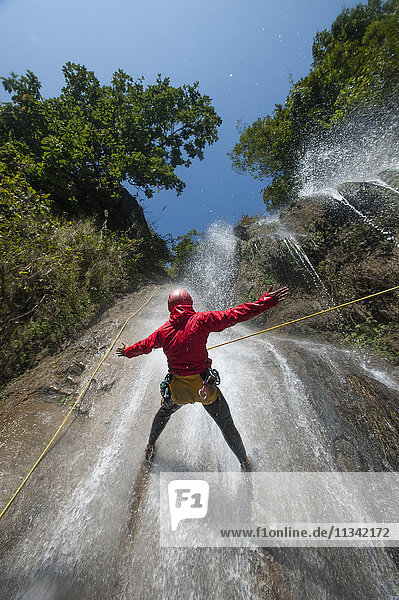 A man pauses to hold his arms in the falling water while canyoning  Nepal  Asia