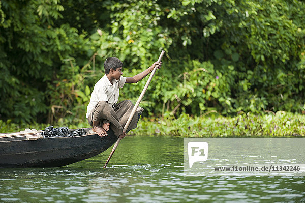 A boy paddles across Kaptai Lake  Chittagong Hill Tracts  Bangladesh  Asia