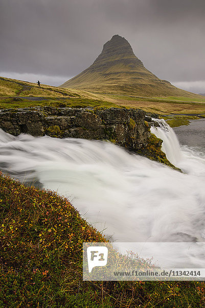 Kirkjufellsfoss in autumn with hiker to show scale  Iceland  Polar Regions