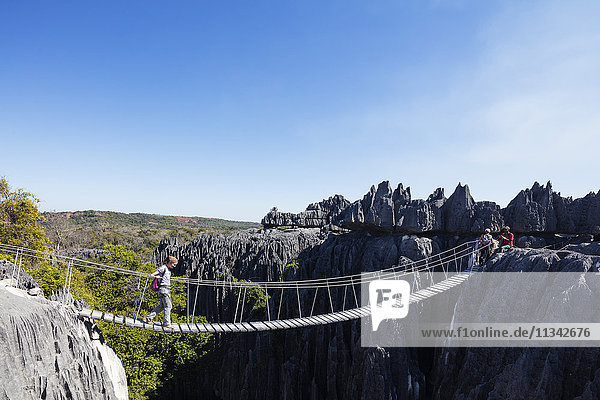 Tourist crossing a rope bridge  Grand Tsingy  Tsingy du Bemaraha National Park  UNESCO World Heritage Site  western area  Madagascar  Africa