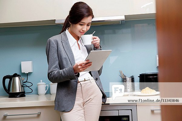 Young women use tablet computers in the kitchen