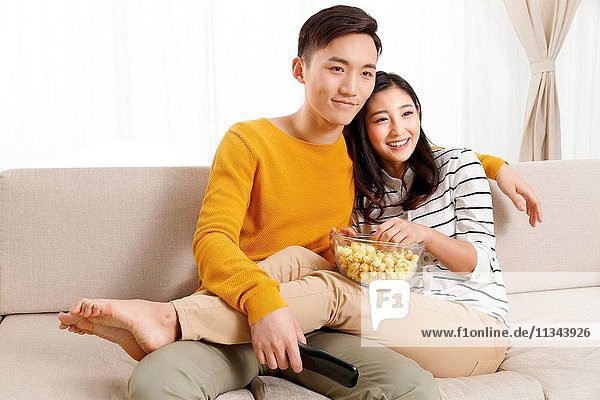 Young couple sitting on the sofa watching TV