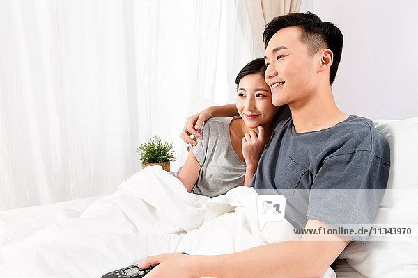 Young couple sitting on the bed watching TV