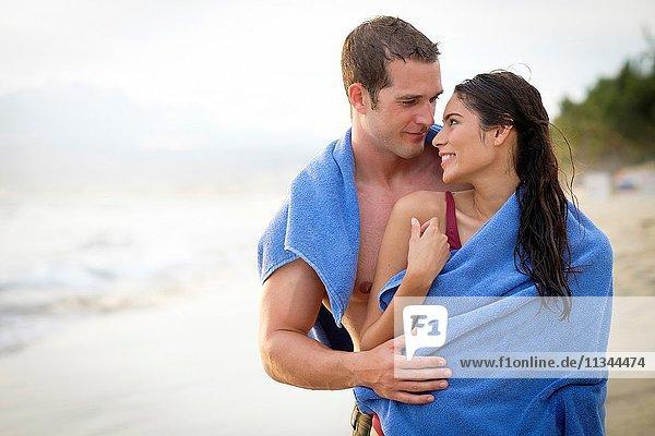 Young couple sharing a towel at a beach at Riviera Nayarit  Mexico.
