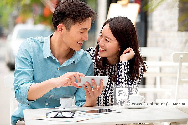 Young couple sitting in a cafe watching mobile phone