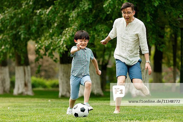 Happy father and son play football on the grass