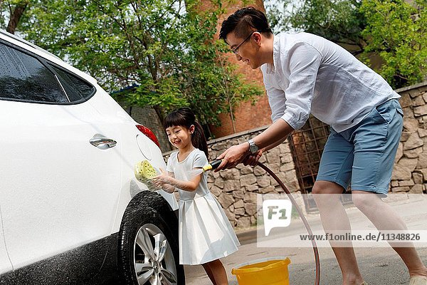 Happy father and daughter to clean the car