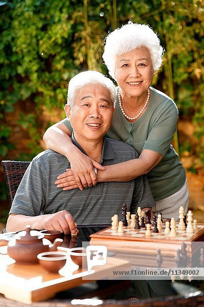 Old couple in the yard to play chess
