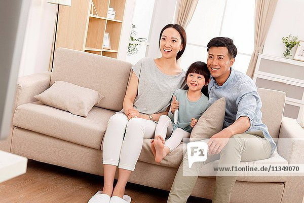 A happy family of three in the living room watching TV.