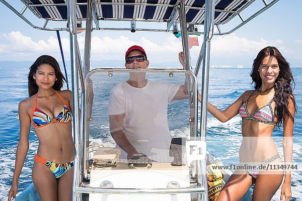 Two young women posing with male captain on small fishing boat. Banderas Bay - Pacific Ocean  Puerto Vallarta  Mexico.