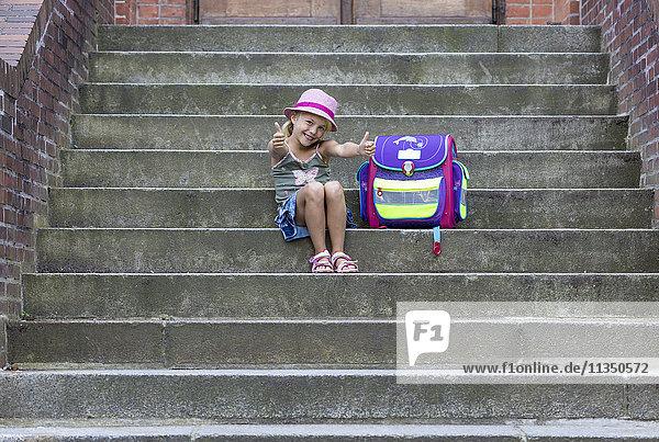 Mädchen sitzt mit Schulranzen auf der Treppe  Kiel  Schleswig-Holstein  Deutschland  Europa