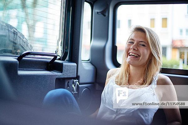Portrait einer fröhlichen jungen Frau in einem Auto