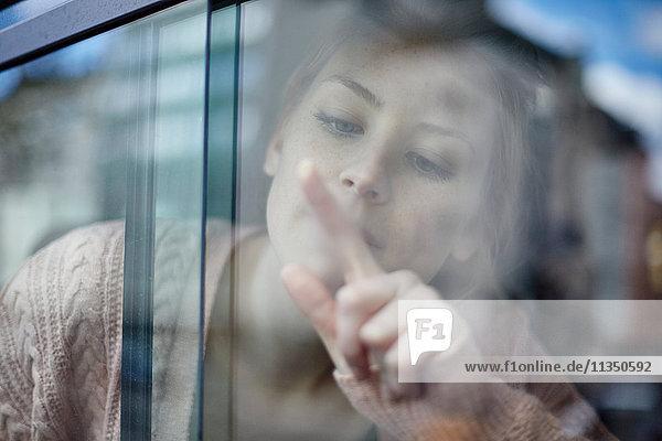 Junge Frau hinter einem Autofenster zeichnet an die Scheibe