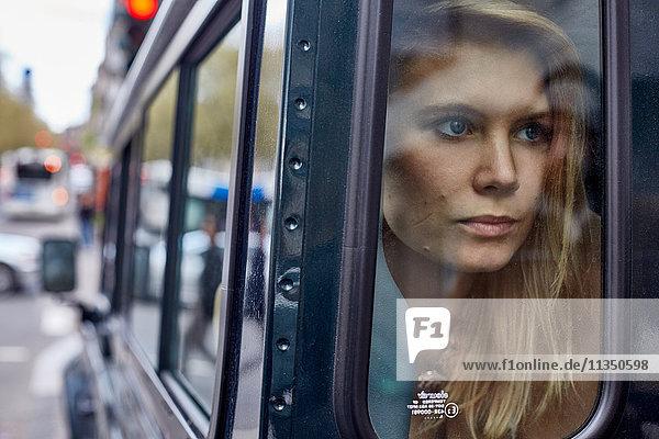 Junge Frau hinter einem Autofenster schaut hinaus