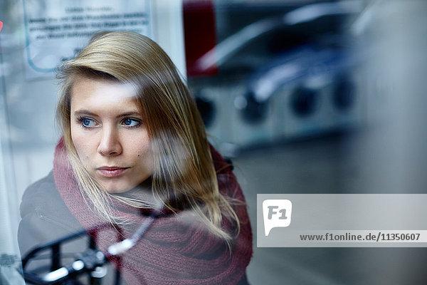 Junge Frau hinter einer Fensterscheibe