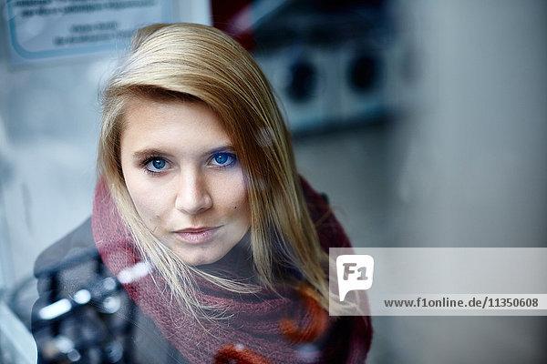 Portrait einer jungen Frau hinter einer Fensterscheibe