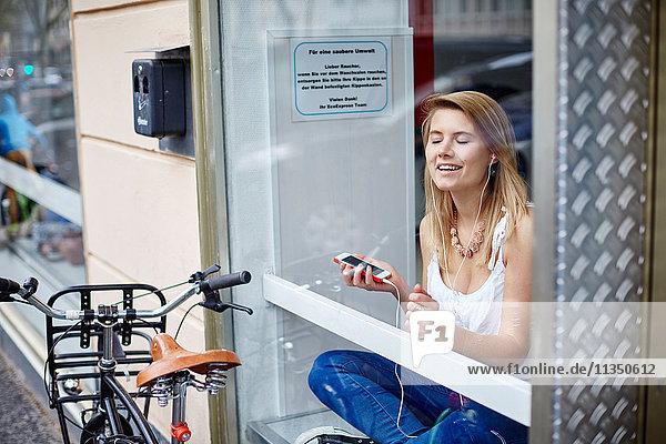 Junge Frau hinter einer Fensterscheibe hört Musik