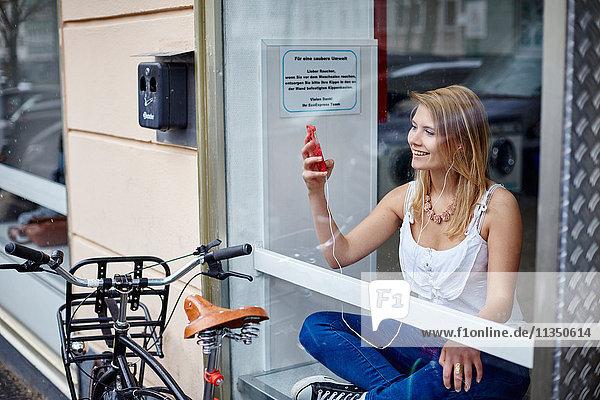 Junge Frau mit Handy und Ohrhörern hinter einer Fensterscheibe