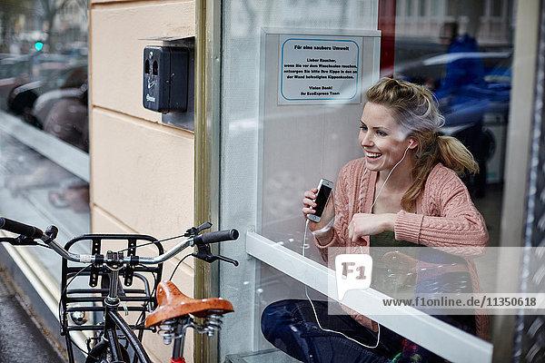 Fröhliche junge Frau hinter einer Fensterscheibe hört Musik