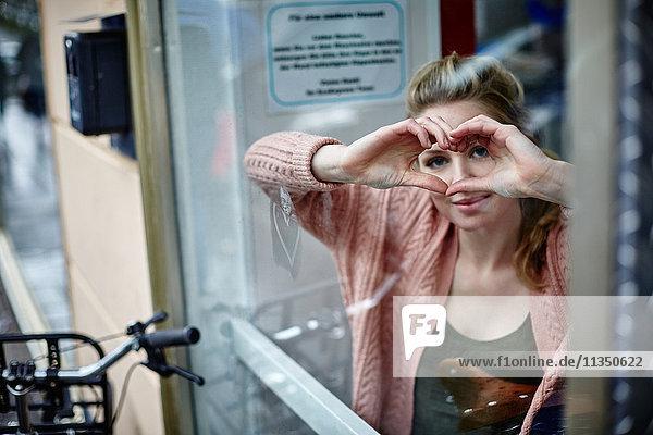 Junge Frau hinter einer Fensterscheibe formt ein Herz mit ihren Händen