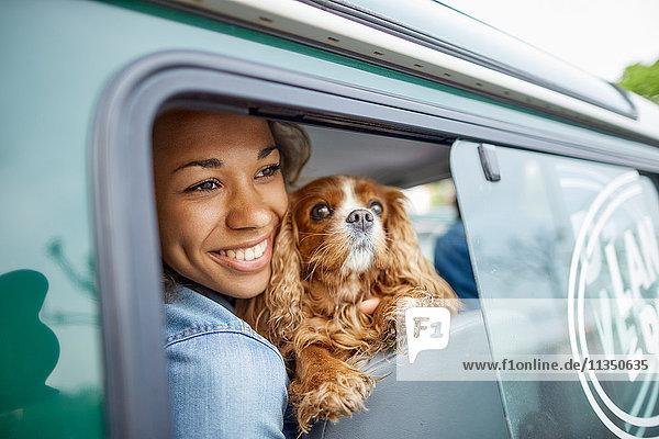 Fröhliche junge Frau mit Hund im Auto schaut aus dem Fenster