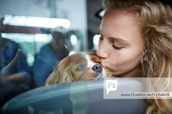 Junge Frau küsst einen Hund im Auto