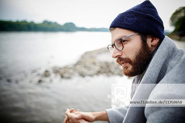 Junger Mann mit Vollbart am Flussufer