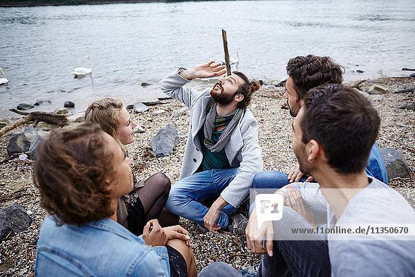 Mann sitzt mit Freunden am Flussufer und balanciert einen Stock auf seinem Kopf