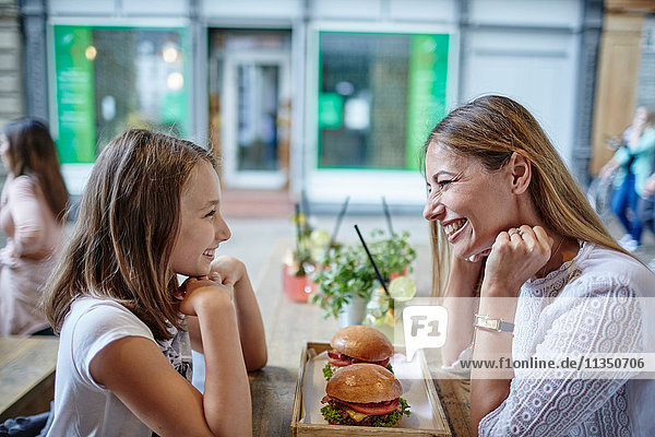 Glückliche Mutter und Tochter sitzen im Restaurant mit Hamburgern