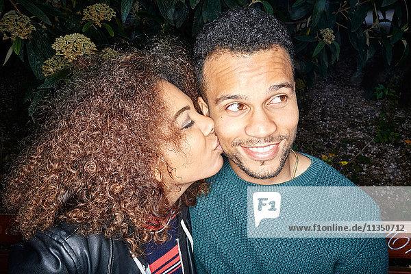 Junge Frau küsst Mann im Freien
