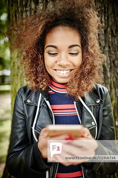 Happy young woman looking on cell phone