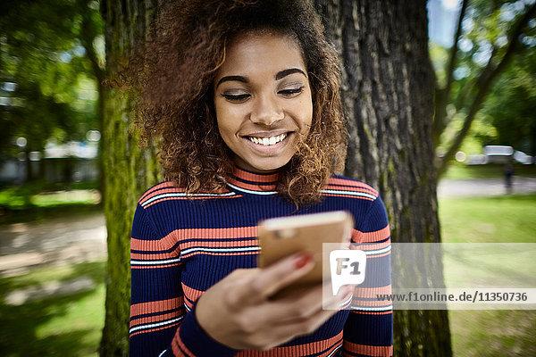 Glückliche junge Frau schaut auf ihr Handy