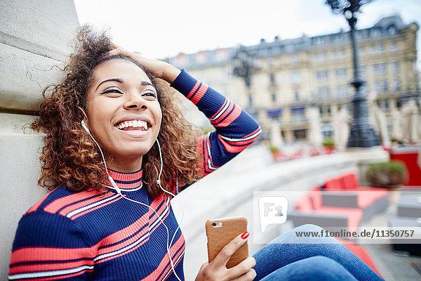 Fröhliche junge Frau hört Musik im Freien