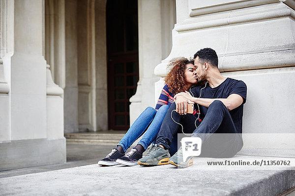 Sitzendes junges Paar küsst sich