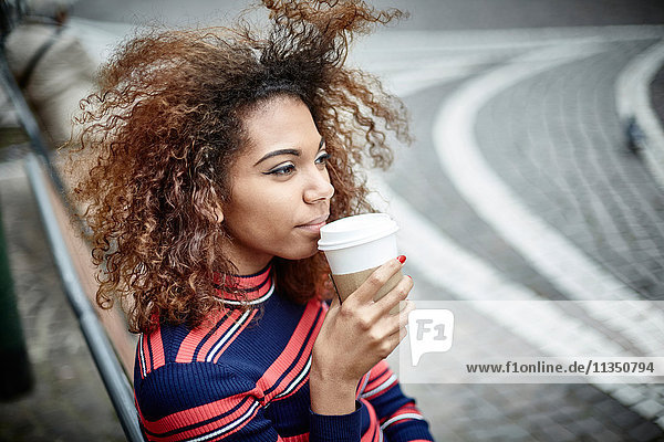 Young woman in the city with takeaway coffee