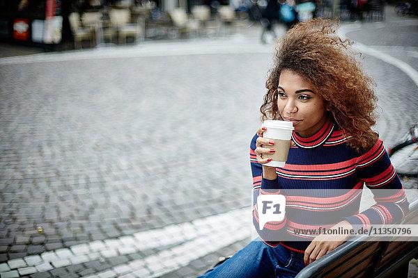 Junge Frau in der Stadt mit Coffee to go
