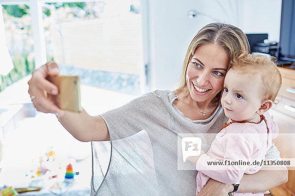 Glückliche Mutter mit Baby macht ein Selfie