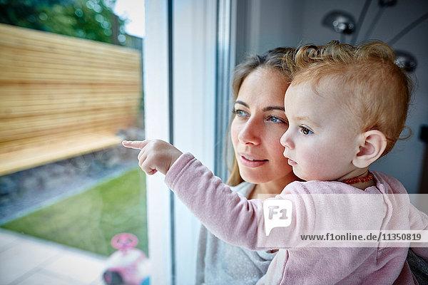 Mutter und Baby schauen aus dem Fenster