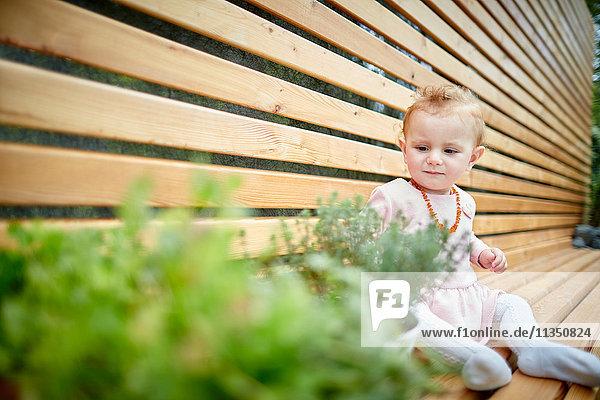 Baby sitzt auf einer Bank neben Topfpflanzen