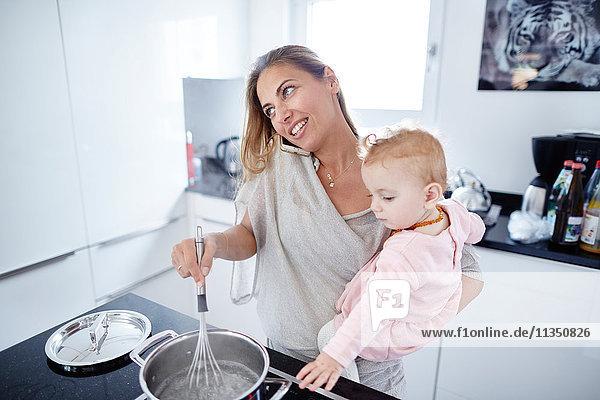 Mutter mit Baby kocht und telefoniert