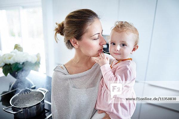 Mutter und Baby teilen sich eine Spaghetti-Nudel