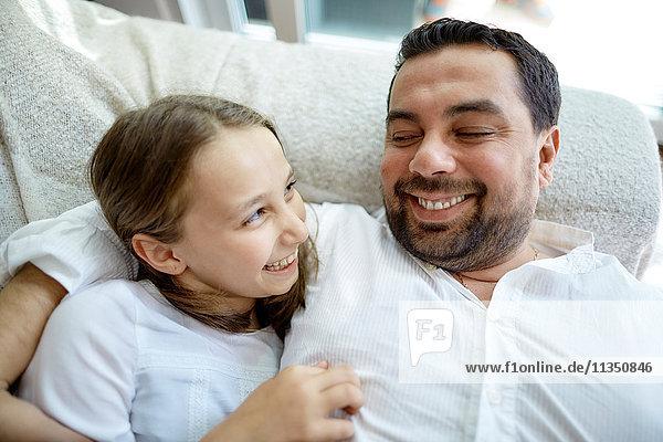 Fröhlicher Vater und Tochter liegen Zuhause