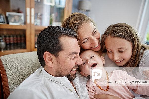 Fröhliche Familie mit Baby Zuhause