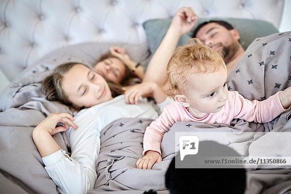Familie mit Baby liegt im Bett
