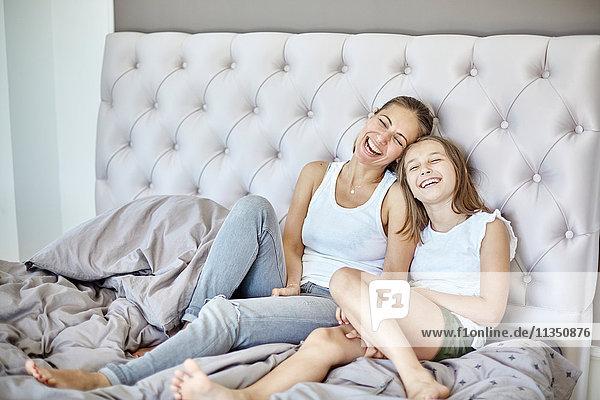 Fröhliche Mutter und Tochter im Bett