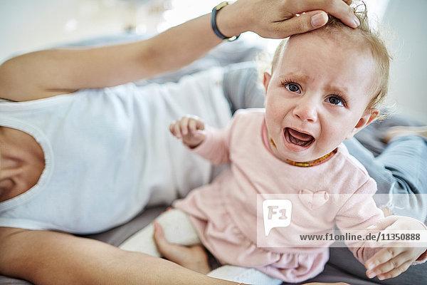 Mutter tröstet weinendes Baby