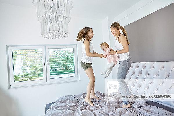 Mutter mit Tochter und Baby springen auf dem Bett