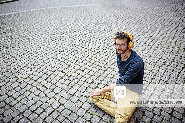 Junger Mann sitzt auf einem Platz und hört Musik