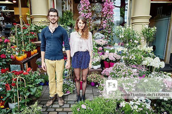 Junges Paar steht an einem Blumengeschäft